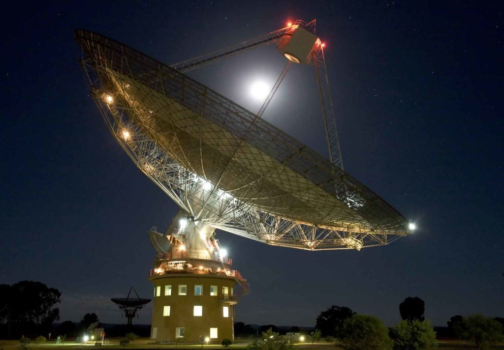 An almost full moon shines brightly above he CSIRO Parkes Radiotelescope.